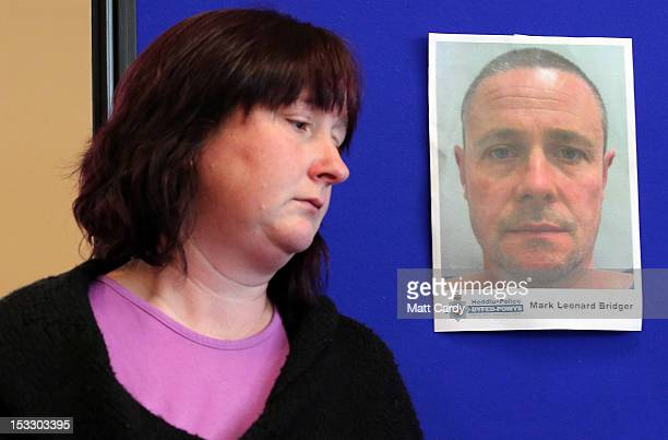 Coral Jones passes a poster showing the face of Mark Leonard Bridger as she prepares to speak at a DyfedPowys Police press conference and appeal for...