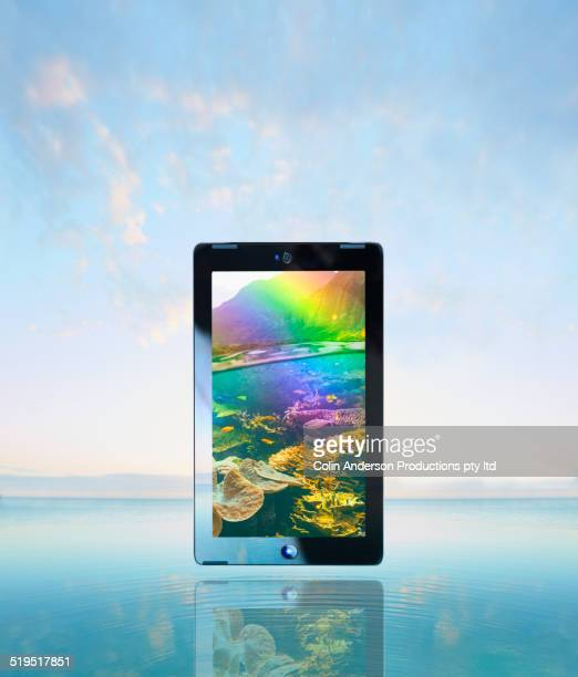 Coral reef and rainbow scene on screen of digital tablet floating over water