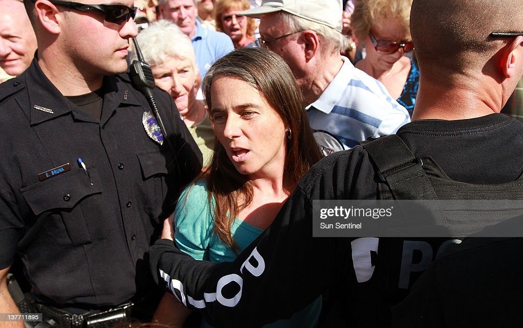 Coral Springs, Florida police escort Cara Jennings of Palm Beach Gardens away after constant shouting at Republican presidential candidate Newt Gingrich during a rally at Wings Plus in Coral Springs, Florida, Wednesday, January 25, 2012.
