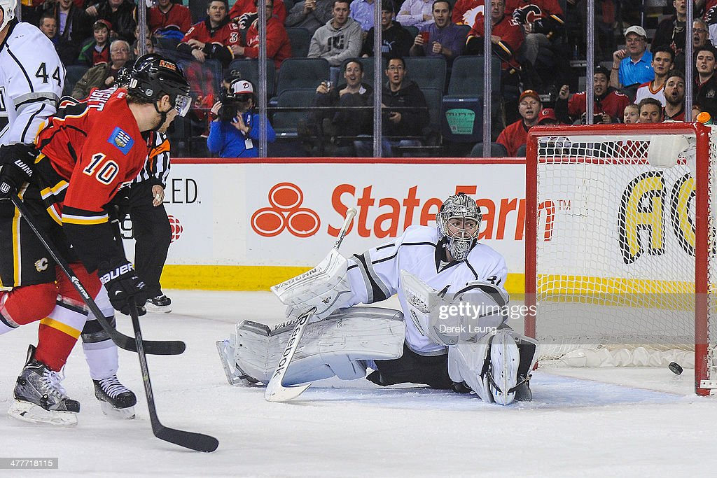 Corban Knight #10 of the Calgary Flames watches the shot of his teammate Brian McGrattan #16 fly past the defence of Martin Jones #31 of the Los Angeles Kings during an NHL game at Scotiabank Saddledome on March 10, 2014 in Calgary, Alberta, Canada. The Kings defeated the Flames 3-2.