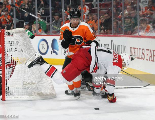 Corban Knight of the Philadelphia Flyers checks Nino Niederreiter of the Carolina Hurricanes behind the net as they battle for the loose puck on...