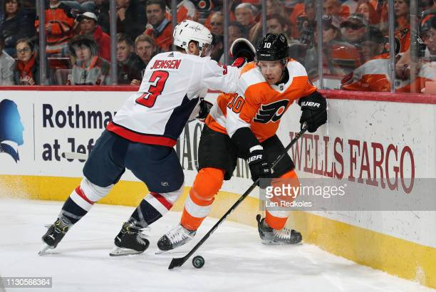 Corban Knight of the Philadelphia Flyers controls the puck along the boards while being checked by Nick Jensen of the Washington Capitals on March 14...