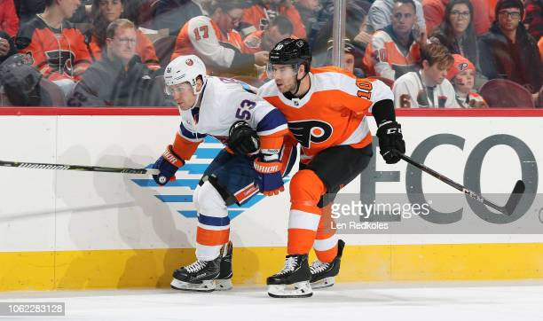 Corban Knight of the Philadelphia Flyers skates along the boards with Casey Cizikas of the New York Islanders on October 27 2018 at the Wells Fargo...