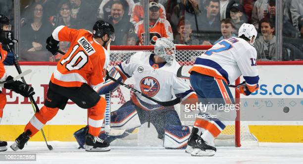Corban Knight of the Philadelphia Flyers takes a shot on goal against Robin Lehner and Matt Martin of the New York Islanders on October 27 2018 at...