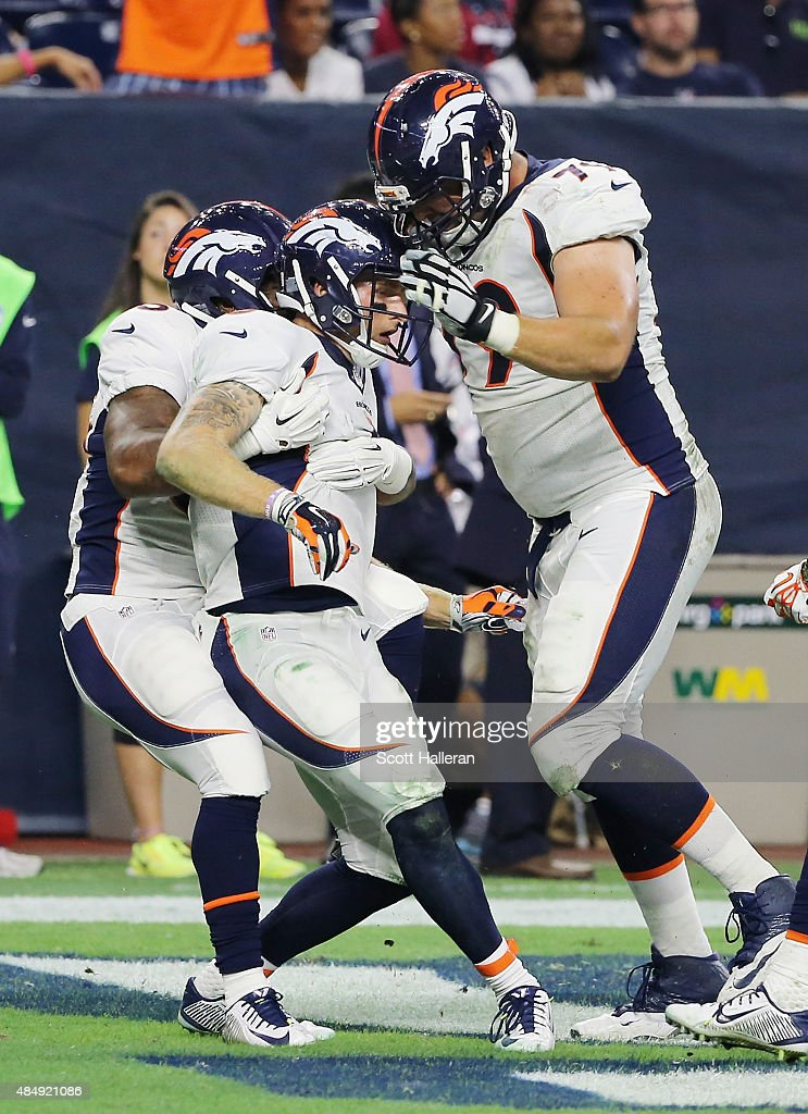 Corbin Louks #6 of the Denver Broncos gets hugged by his teammates after scoring the go-ahead touchdown in the second half of their game against the Houston Texans at NRG Stadium on August 22, 2015 in Houston, Texas.
