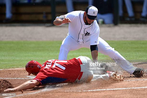Cord Phelps of the Philadelphia Phillies beats a tag by Anibal Sanchez of the Detroit Tigers during a spring training game at Joker Marchant Stadium...