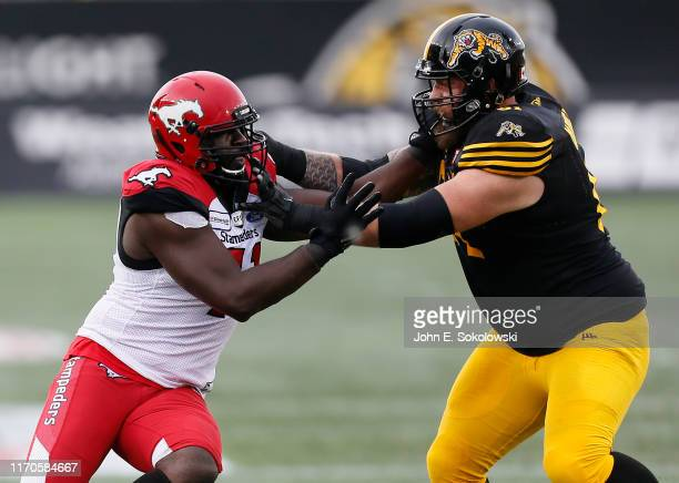 Cordarro Law of the Calgary Stampeders tries to avoid a block by Ryker Mathews of the Hamilton Tiger-Cats at Tim Hortons Field on July 13, 2019 in...