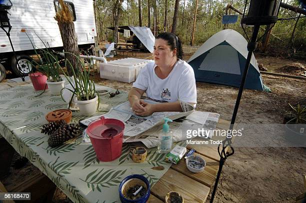 Cordelia Hunnicutt reads the newspaper outside her FEMA trailer in a park November 14 2005 in Kiln Mississippi Hunnicutte sitting near the sewage...