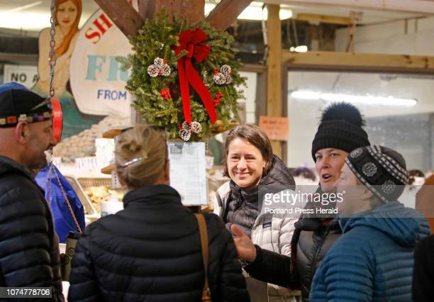 Cordie Southall center of Freeport and Margaret Donahue of Yarmouth catch up with friends while shopping early Sunday morning at Harbor Fish Market...