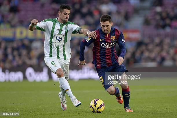 Cordoba's midfielder Luis Eduardo luso Delgado vies with Barcelona's Argentinian forward Lionel Messi during the Spanish league football match FC...