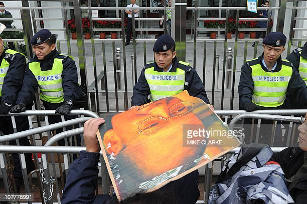 Cordon of police behind portable railings prevent banner wielding protesters from approaching the Chinese liason office in Hong Kong on December 25,...