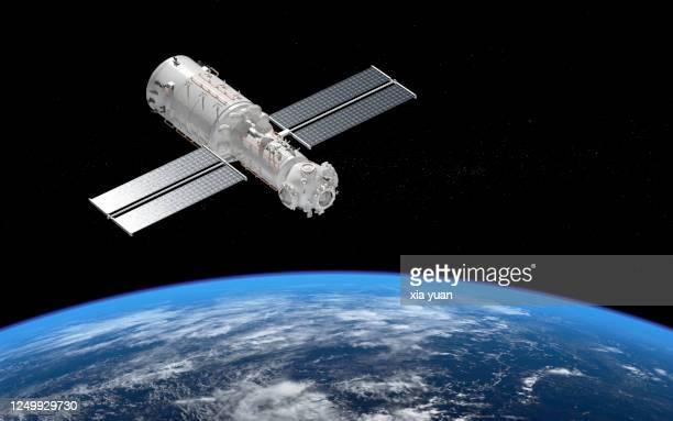 core module of china's space station tianhe orbiting earth - stapellauf stock-fotos und bilder
