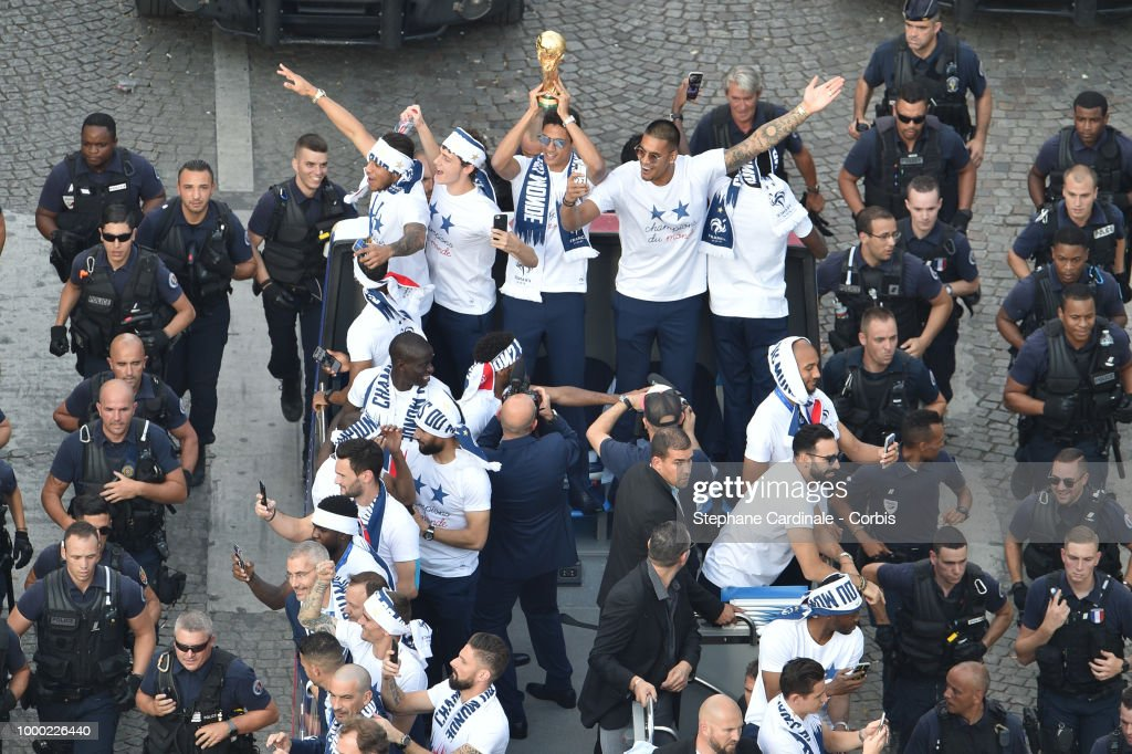 Corentin Tolisso, Benjamin Pavard, Raphael Varane holding the trophy, Alphonse Areola, Blaise Matuidi and Olivier Giroud celebrate with teammates on the roof of a bus as they parade down the Champs-Elysee in Paris on July 16, 2018 at the Champs Elysees in Paris, France.