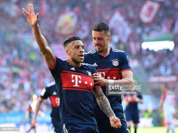 Corentin Tolisso of Bayern Muenchen celebrates scoring his teams first goal with teammate Sandro Wagner during the Bundesliga match between FC...