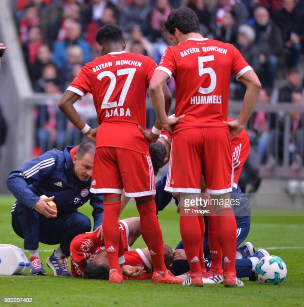 Corentin Tolisso of Bayern Muenchen receives medical help and David Alaba of Bayern Muenchen and Mats Hummels of Bayern Muenchen look on during the...
