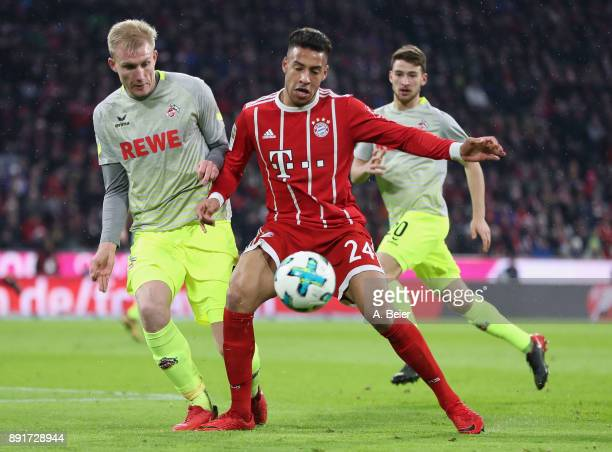 Corentin Tolisso of FC Bayern Muenchen fights for the ball with Frederik Soerensen of 1 FC Koeln during the Bundesliga match between FC Bayern...