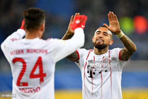 Corentin Tolisso of Muenchen celebrate victory with team mate Arturo Vidal after the DFB Cup quarter final match between SC Paderborn and Bayern...