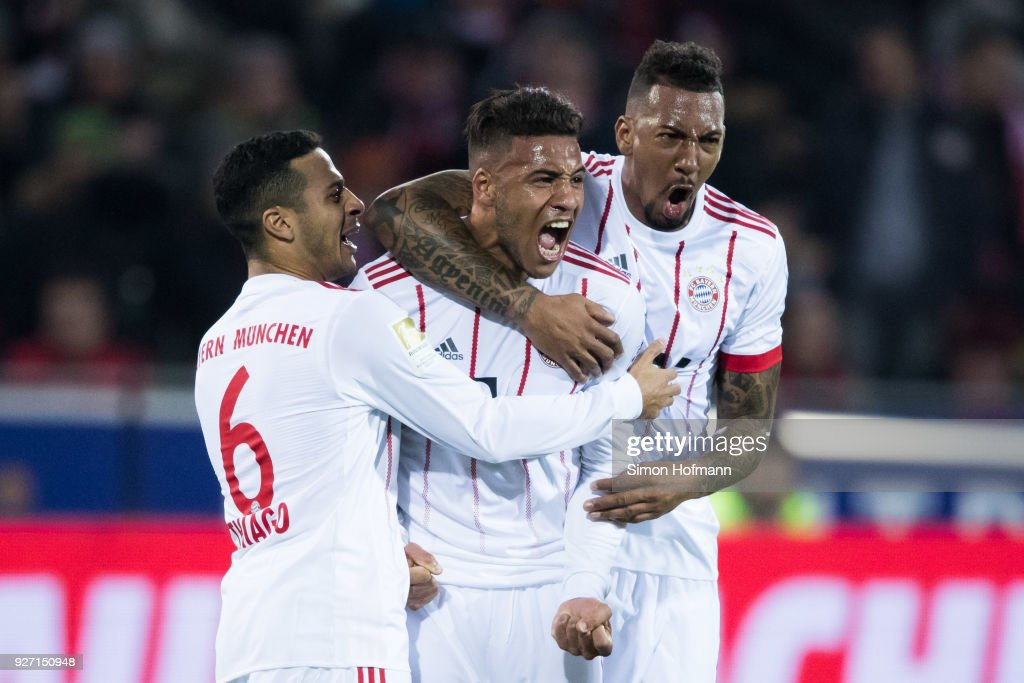 Corentin Tolisso of Muenchen celebrates his team's second goal with team mates Jerome Boateng (R) and Thiago (L) during the Bundesliga match between Sport-Club Freiburg and FC Bayern Muenchen at Schwarzwald-Stadion on March 4, 2018 in Freiburg im Breisgau, Germany.
