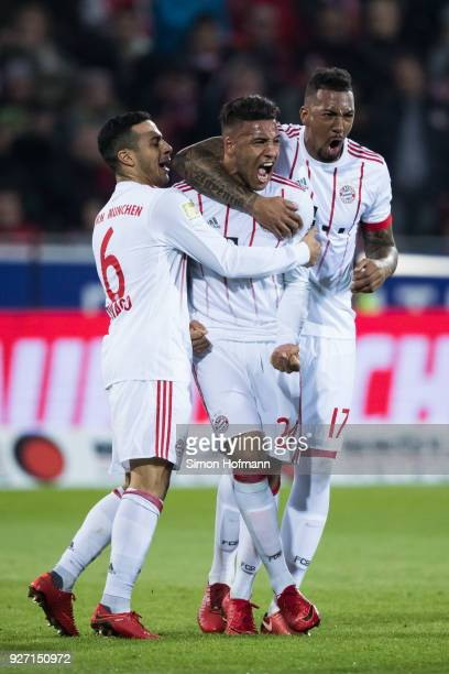 Corentin Tolisso of Muenchen celebrates his team's second goal with team mates Jerome Boateng and Thiago during the Bundesliga match between...