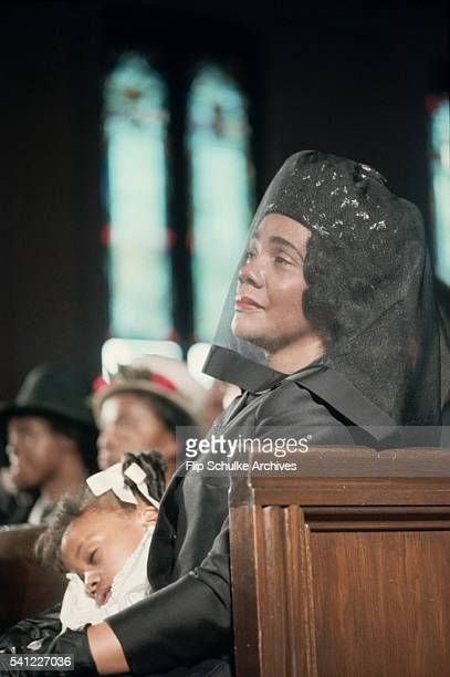 Coretta Scott King holds her sleeping daughter Bernice at the funeral of her husband Martin Luther King Jr His brother AD King sits beside them
