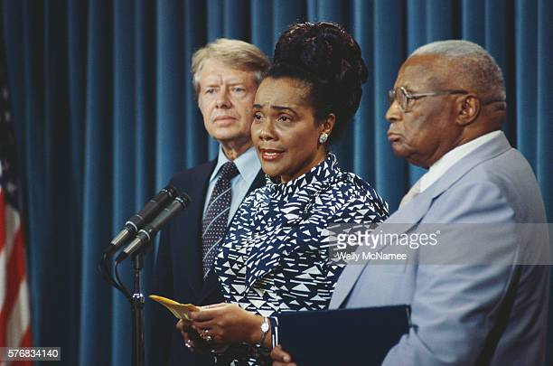 Coretta Scott King speaks at a microphone flanked by President Jimmy Carter and her fatherinlaw Martin Luther King Sr