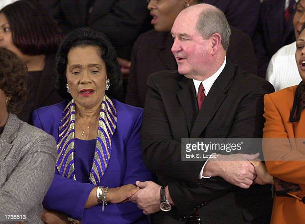 Coretta Scott King widow of slain civil rights leader Rev Martin Luther King joins hands and sings with Georgia Gov Sonny Perdue during the Martin...