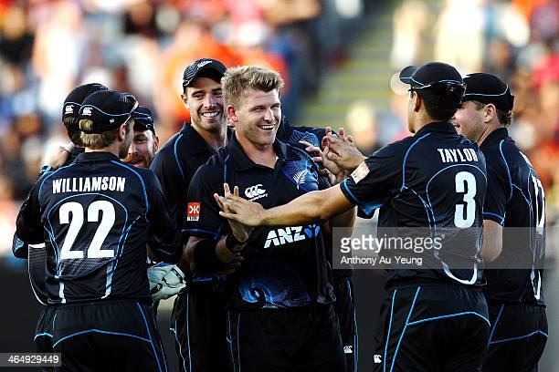 Corey Anderson of New Zealand is mobbed by his teammates after taking the wicket of Ajinkya Rahane of India during the One Day International match...