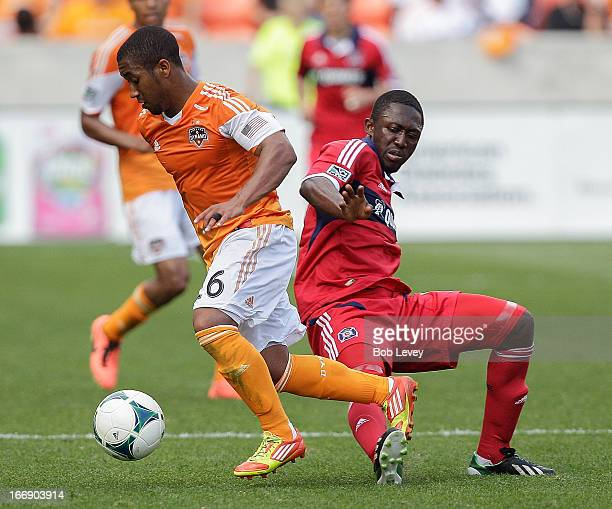 Corey Ashe of the Houston Dynamo puts a move on Patrick Nyarko of the Chicago Fire at BBVA Compass Stadium on April 14 2013 in Houston Texas...