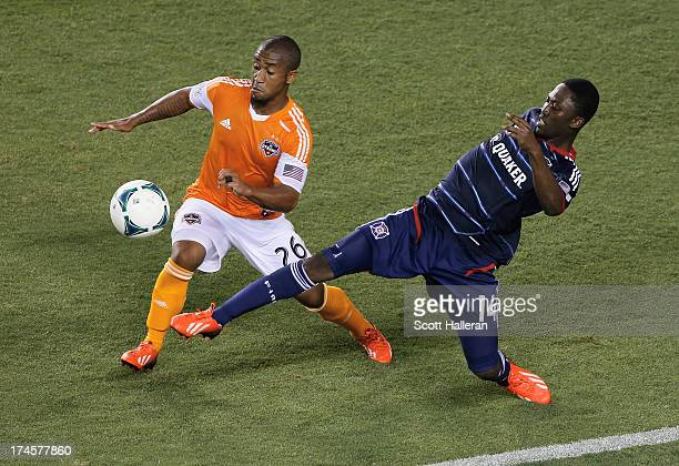 Corey Ashe of the Houston Dynamo works the ball against Patrick Nyarko of the Chicago Fire at BBVA Compass Stadium on July 27 2013 in Houston Texas