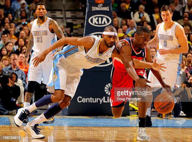 Corey Brewer of the Denver Nuggets and Jordan Crawford of the Washington Wizards battle for a loose ball at the Pepsi Center on January 18 2013 in...