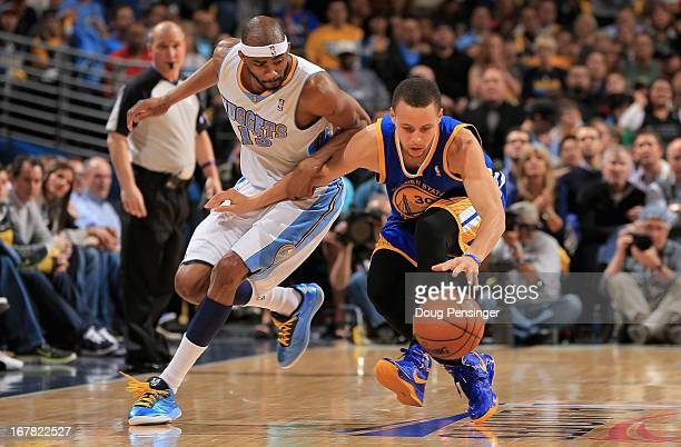 Corey Brewer of the Denver Nuggets and Stephen Curry of the Golden State Warriors vie for a loose ball during Game Five of the Western Conference...