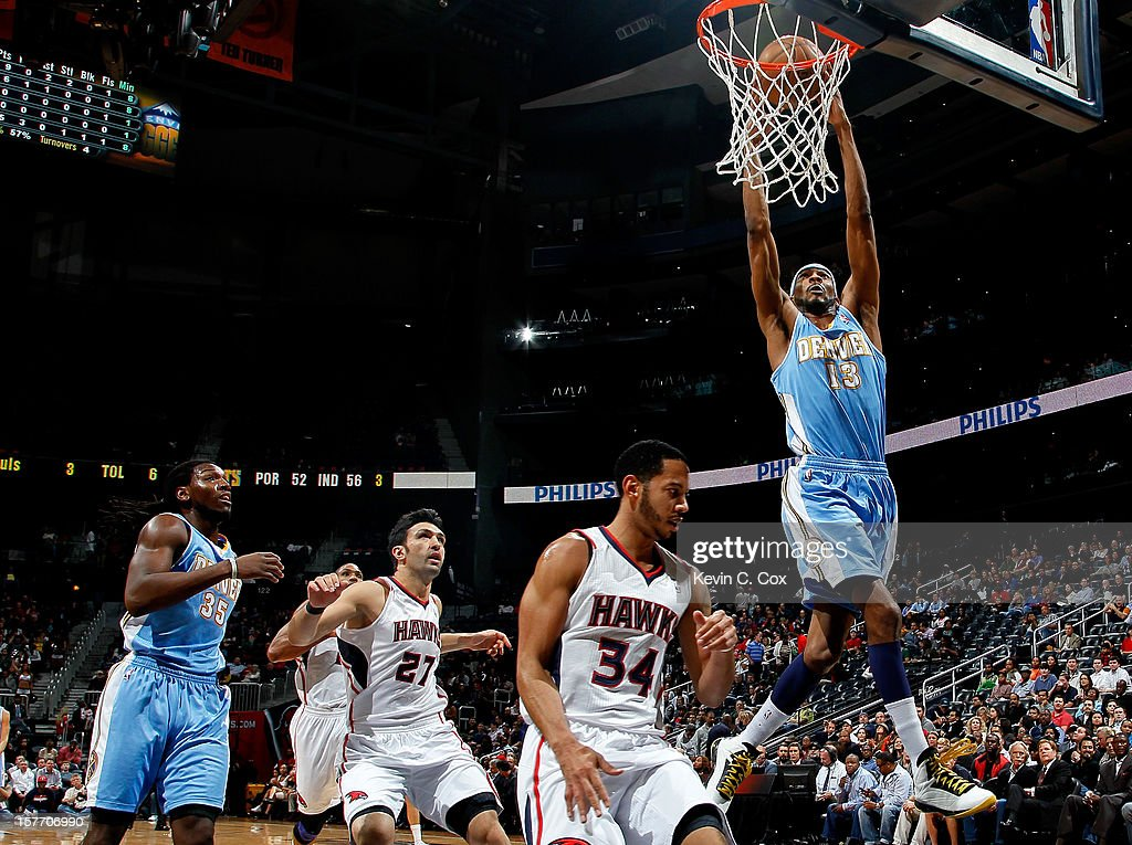 Corey Brewer #13 of the Denver Nuggets dunks against Devin Harris #34 of the Atlanta Hawks at Philips Arena on December 5, 2012 in Atlanta, Georgia.
