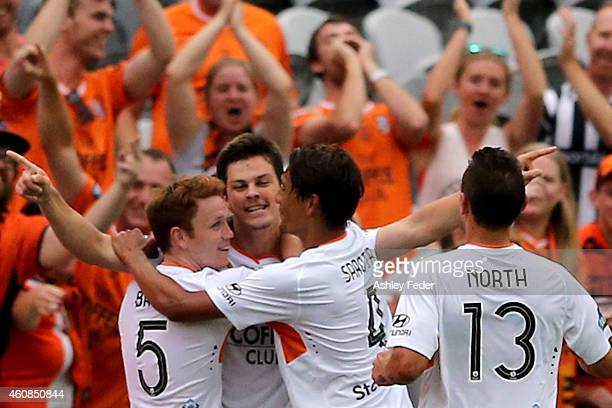 Corey Brown and Jean Carlos Solorzano of the Roar celebrate a goal with fans during the round 13 A-League match between the Central Coast Mariners...