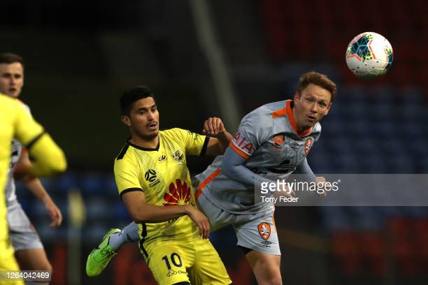 Corey Brown of Brisbane Roar contests the ball with Ulises Davila of Wellington Phoenix during the round 28 A-League match between the Wellington...