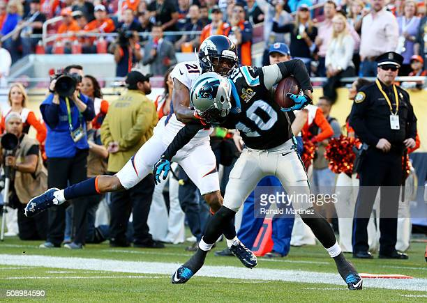 Corey Brown of the Carolina Panthers runs after a catch as Aqib Talib of the Denver Broncos grabs his facemask during the tackle in the second...