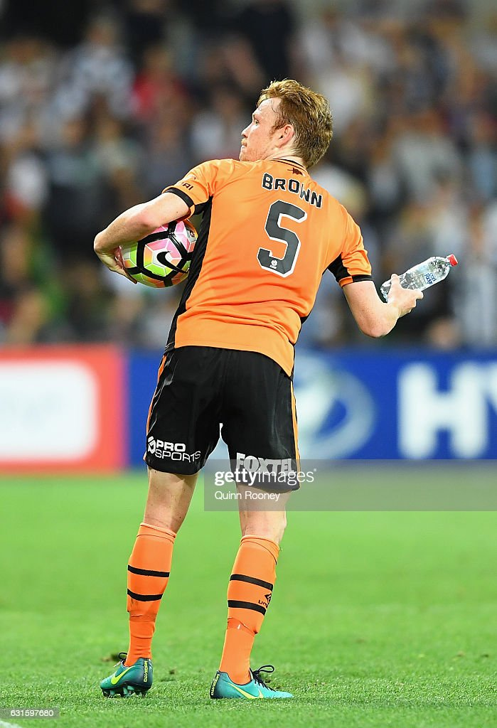 Corey Brown of the Roar picks up a bottle that was thrown at him during the round 15 A-League match between the Melbourne Victory and the Brisbane Roar at AAMI Park on January 13, 2017 in Melbourne, Australia.