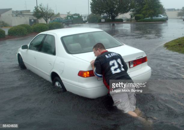 Corey Burnheart tries to push a stalled car off a street flooded by heavy rainfall caused by Hurricane Ophelia as it moves closer to the North...