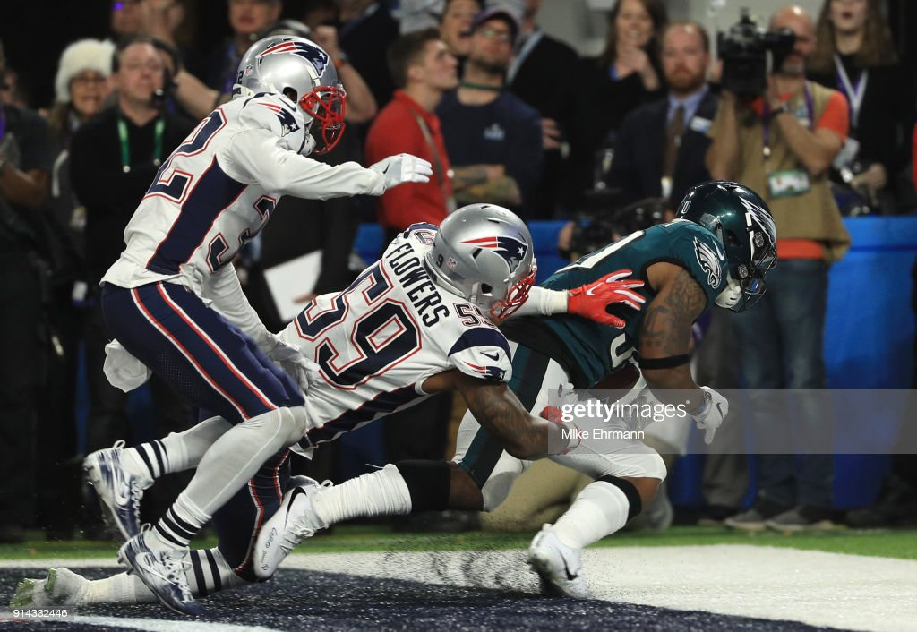 Corey Clement #30 of the Philadelphia Eagles catches a 22 yard touchdown pass against Marquis Flowers #59 and Patrick Chung #23 of the New England Patriots during the third quarter in Super Bowl LII at U.S. Bank Stadium on February 4, 2018 in Minneapolis, Minnesota.