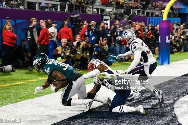 Corey Clement of the Philadelphia Eagles catches a 22yard touchdown pass past Marquis Flowers and Patrick Chung of the New England Patriots during...