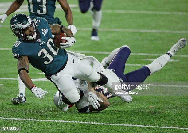 Corey Clement of the Philadelphia Eagles is tripped up by Patrick Chung of the New England Patriots during Super Bowl Lll at US Bank Stadium on...