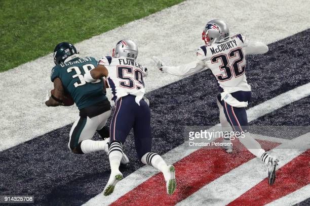 Corey Clement of the Philadelphia Eagles scores a 22yard touchdown against Marquis Flowers and Devin McCourty of the New England Patriots in the...