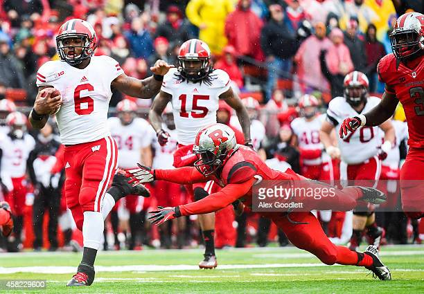 Corey Clement of the Wisconsin Badgers runs past Gareef Glashen of the Rutgers Scarlet Knights before scoring a touchdown in the second quarter at...