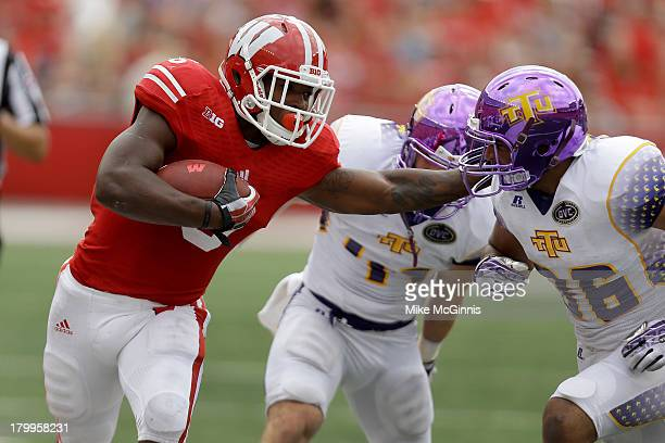 Corey Clement of the Wisconsin Badgers stiff arms Tevin McDermott of the Tennessee Tech Golden Eagles while running upfield during the game at Camp...