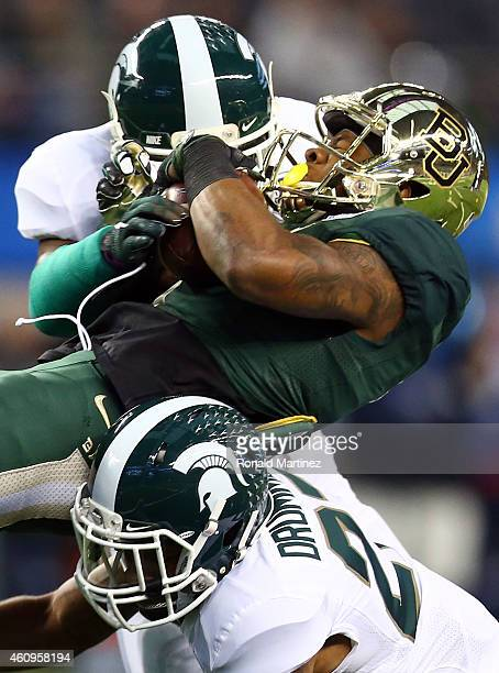 Corey Coleman of the Baylor Bears is hit by Mylan Hicks of the Michigan State Spartans and Kurtis Drummond of the Michigan State Spartans during the...