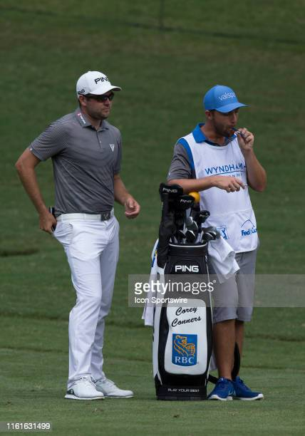 Corey Conners and his caddie Kyle Peters survey the yardage from the 11th fairway during the final round of the Wyndham Championship on August 04...