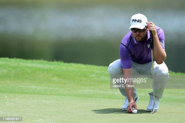 Corey Conners of Canada lines up a putt attempt on the 15th green during the first round of the Wyndham Championship at Sedgefield Country Club on...