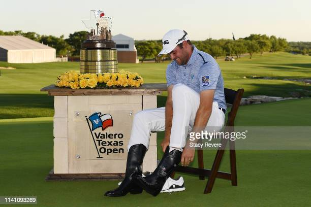 Corey Conners of Canada puts on the Champion's boots after winning the 2019 Valero Texas Open at TPC San Antonio Oaks Course on April 07 2019 in San...