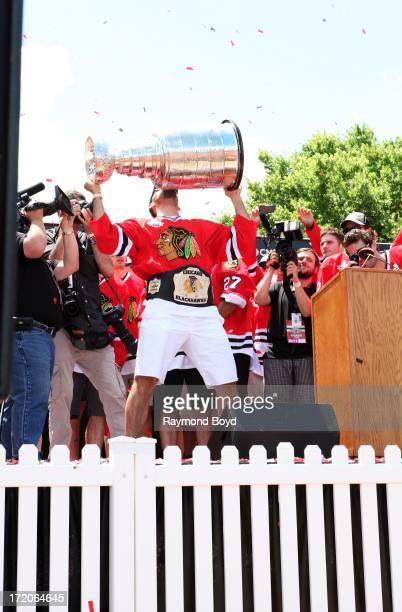 Corey Crawford goalie for the Chicago Blackhawks raises and kisses the Stanley Cup Trophy during the Chicago Blackhawks' 2013 Stanley Cup...