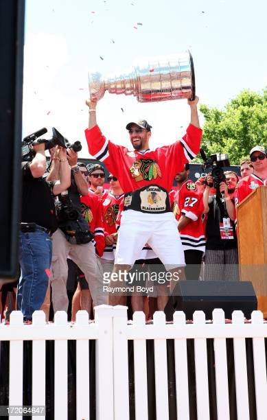 Corey Crawford goalie for the Chicago Blackhawks raises the Stanley Cup Trophy during the Chicago Blackhawks' 2013 Stanley Cup Championship rally at...