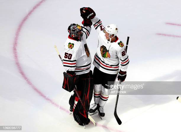 Corey Crawford of the Chicago Blackhawks celebrates the 6-4 win over the Edmonton Oilers with teammate Adam Boqvist after Game One of the Western...